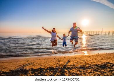 happy family jump on the shore on sunset light