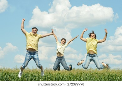 Happy family jumping outdoors against the sky
