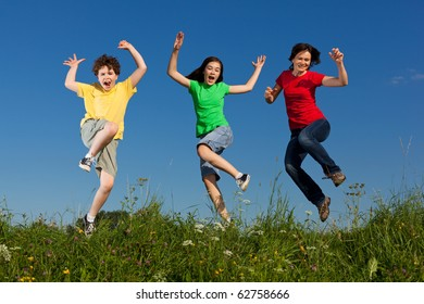 Happy family jumping, running outdoor