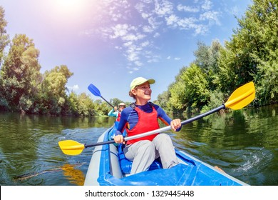 Happy family kayaking on the river. Active girl with her mother having fun enjoying adventurous experience with kayak on a sunny day during summer vacation
