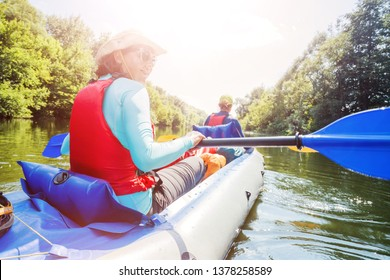 Happy family kayaking on the river. Active woman with her daughter having fun enjoying adventurous experience with kayak on a sunny day during summer vacation