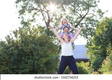 A Happy Family with Kid on shoulders outdoors