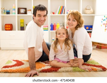Happy family with a kid sitting on the floor together