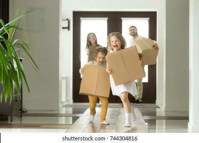 Happy family with kids bought new home, excited children funny girl and boy holding boxes running into big modern house, helping parents with belongings, moving day concept, mortgage and relocation