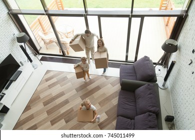 Happy family with kids carrying boxes entering into big modern house with glass wall and terrace, children helping parents holding belongings, moving in day concept, mortgage and relocation, top view