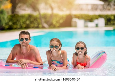 Happy family of kids and father in swimming pool