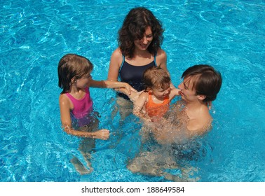 Happy family with kids in pool having fun, summer vacation