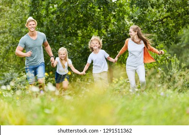 Happy family and kids run together in the garden in summer