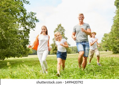 Happy family and kids run together over a summer meadow