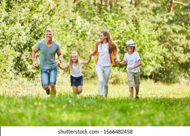 Happy family and kids run together over meadow in summer