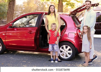 Happy family with kids sitting in car on sunny day