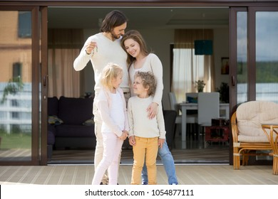 Happy family with kids standing outdoor holding keys of big country house, smiling luxury real estate owners couple and children embracing on terrace after buying new home, mortgage loan concept