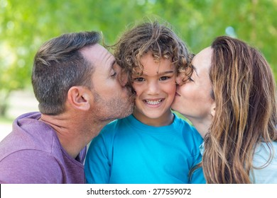 Happy family kissing at camera in the park on a sunny day