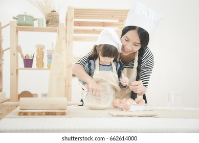 Happy family in the kitchen. Asian mother and her daughter preparing the dough to make a cake.