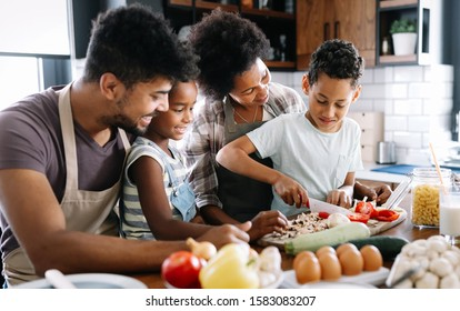 Happy family in the kitchen having fun and cooking together. Healthy food at home. - Shutterstock ID 1583083207