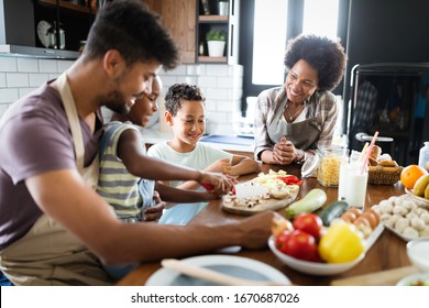 Happy family in the kitchen having fun and cooking together. Healthy food at home.