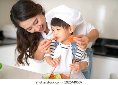 Happy family in the kitchen. Mother and child daughter are preparing the vegetables and fruit.