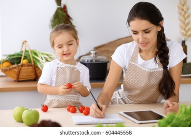Happy family in the kitchen. Mother and child daughter make menue for cooking tasty breakfast in the kitchen