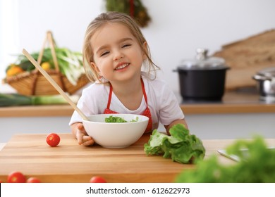 Happy family in the kitchen. Mother and child daughter make menu for cooking tasty breakfast in the kitchen