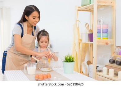Happy family in the kitchen. mother and child daughter cooking preparing the dough, bake cookies in kitchen