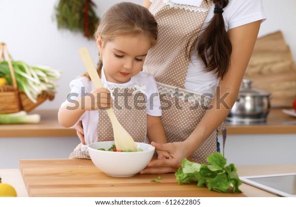 台所で幸せな家族。新鮮なサラダのおいしい朝食を作る母子の娘