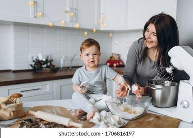 happy family in the kitchen. mother and son preparing the dough, bake cookies