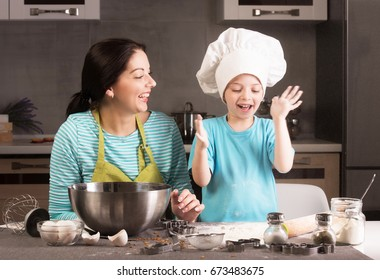 Happy family in the kitchen. Mother and son in chef hat.