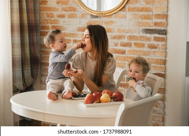 Happy family in the kitchen at the table, eating fruits, vitamins. Beautiful young mother feeds the children boys. Modern interior cozy house, kitchen. Healthy food, complementary foods, vegan food.