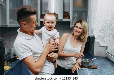 Happy family at kitchen. Young parents feeding their adorable daughter. Love, happiness, parenthood, children concept