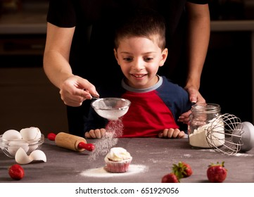 Happy family in the kitchen.Mother and child preparing cookies in kitchen. Mother pouring sugar powder like a snow.
