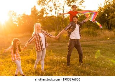 Fröhliche Familie mit Drachen bei Sonnenuntergang auf dem Feld