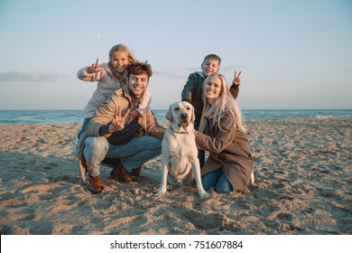 happy family with labrador dog showing peace symbols at seaside