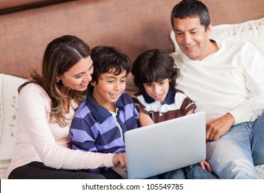 Happy family with a laptop computer in bed