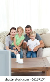 Happy family laughing while watching television sitting on the sofa at home