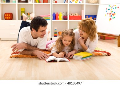 Happy family laying on the floor reading in the kids room