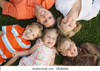 Happy family laying on the grass with heads close together