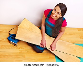 Happy family laying parquet at home.