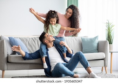 Happy Family Leisure. Cheerful arabic mom, dad and daughter having fun together