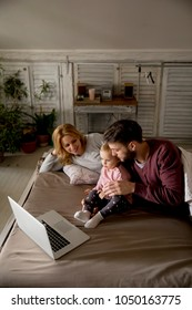 Happy family lies on bed and watching something on laptop in the bedroom