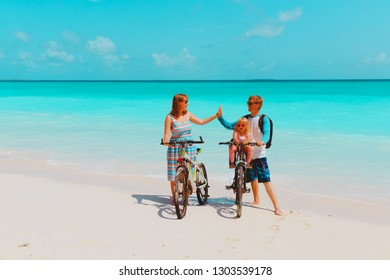 happy family with little baby girl riding bikes on beach