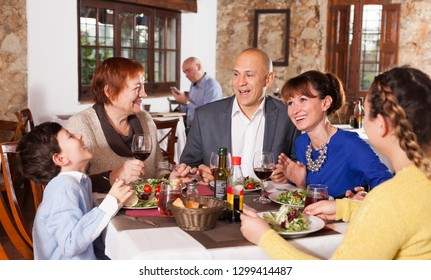 Happy family with little boy and mature grandmother having dinner and nice talking at restaurant