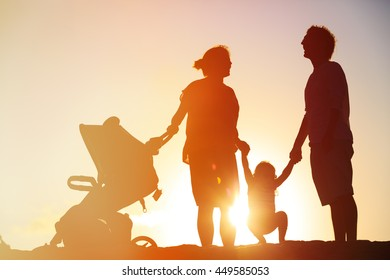 Happy family with little child and stroller play at sunset