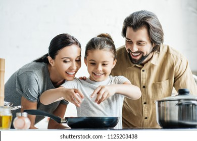happy family with little daughter cooking omelet at kitchen