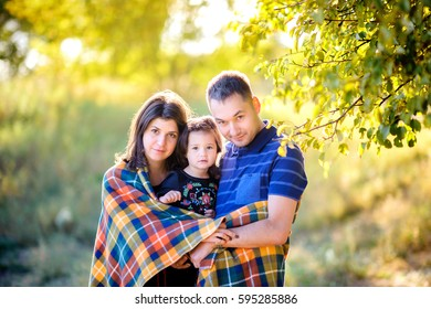 happy family with the little daughter walks in the evening park on a sunset, embrace and take cover a warm plet