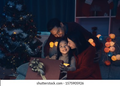 Happy family and little girl open magic gift box with light shining and kiss in living room that decorated with Christmas tree for Christmas festival coming soon, Asian Christmas family concept