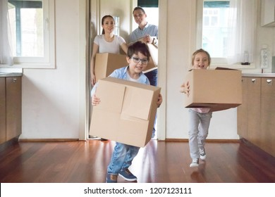 Happy family with little kids arrive at new modern home. Excited funny daughter and son holds carton boxes with belongings helps to parents running inside house. Moving relocation day mortgage concept