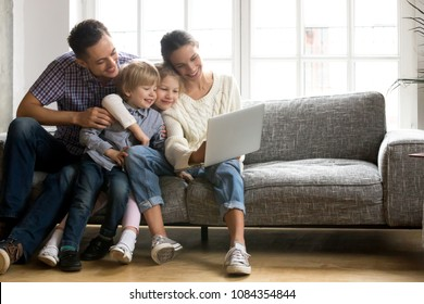Happy family with little kids enjoying using application on laptop together, smiling parents spending time with children son and daughter having fun watching video or doing internet shopping at home