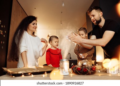 Happy family with little kids at the kitchen. Caring mother and father cooking with wonderful children, smiling. Beautiful parents with son and daughter baking cookies for Christmas, winter holidays