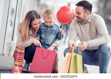 Happy family with little son and shopping bags in city.Sale,consumerism and people concept.