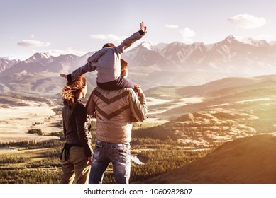 Happy family with little son stands against mountains sunset. Travel tourism adventures concept